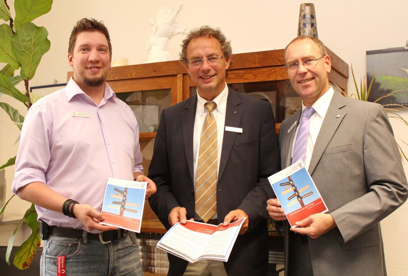 Christian Stokuca (links) und Joachim Hebgen (rechts) vom Amt für Jugend, Schule und Familie überreichten die ersten Schulbroschüren an Landrat Manfred Michel.